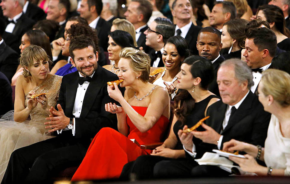 Jennifer Lawrence eats and Bradley Cooper looks on.